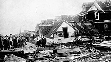 Photograph of a city street showing several damaged homes and piles of rubble, Regina, 1912