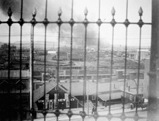 Photograph, taken through a fence, showing view of city of Ottawa and distant smoke in Hull, 1900