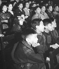 Photograph of children and some adults watching a film; seated in six rows of chairs, approximately 15 chairs in each row