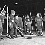 Photograph of a man teaching several young boys wearing skates and hockey jerseys, 1956