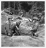 Photograph of a three-inch (7.62 cm) mortar crew of Support Company, The Regina Rifle Regiment. Bretteville-l�Orgueilleuse, France, circa June 9, 1944. Photograph by Lieutenant Donald I. Grant.