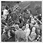 Photograph of two infantrymen of The West Nova Scotia Regiment in a Universal Carrier en route to Rotterdam, surrounded by Dutch civilians celebrating the liberation of the Netherlands, May 9, 1945. Photograph by Lieutenant G. Barry Gilroy.