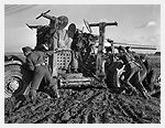 Photograph of gunners of the 2nd Heavy Anti-Aircraft Regiment, Royal Canadian Artillery, pushing a 3.7-inch (9.84 cm) anti-aircraft gun through mud. Dunkerque, France, February 1, 1945. Photograph by Lieutenant Ken Bell.