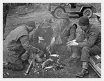 Photograph of four infantrymen of The Argyll and Sutherland Highlanders of Canada cooking a meal and warming themselves around a fire in a barnyard near Veen, Germany, March 7, 1945. Photograph by Captain Jack H. Smith.