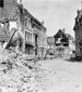 Photograph of rubble and heavily damaged buildings along street in Ypres, July 1916