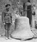 Photograph of an unidentified soldier standing beside the damaged bell of St. Peter's Church, Ypres, August 1916