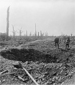 Photograph of two Canadians examining the shell-damaged road to Bapaume, October 1916