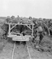 Photograph of Canadians bringing wounded comrades to the Field Dressing Station on a light track cart, Vimy Ridge, April 1917