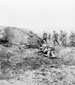 Photograph of tank and advancing infantry. An unidentified slain soldier lies in the foreground. Vimy Ridge, April 1917