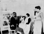 Photograph of Dr. Wilfred Grenfell examining young patient, in company of nurses, circa 1905-1915, Harrington Harbour, [Quebec]