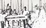 Photograph of lepers holding a banner bearing the words: 'Merci au docteur Gingras'