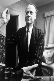 Photograph of McLuhan holding a mirror that contains his reflection, 1967, by John Reeves