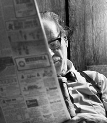 Photograph of Marshall McLuhan reading newspaper, December 1972, by Lou Forsdale