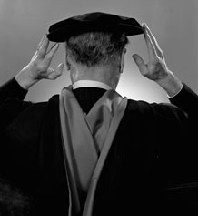 Photograph (rear view) of Marshall McLuhan adjusting his university cap, January 21, 1967, by Yousuf Karsh