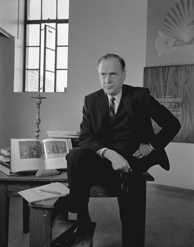Photograph of Marshall McLuhan posing at table with books, January 21, 1967, by Yousuf Karsh