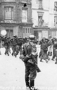 German soldiers keep Canadian prisoners of war under surveillance as they are led through Dieppe.