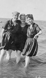 Photograph of three women in bathing dresses and caps standing in ankle-deep water, Grand Beach, Lake Winnipeg, Manitoba, circa 1914