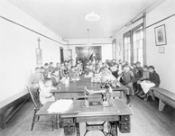 Black and white photograph of a group of girls seated around a large table; a sewing machine table is visible in the foreground