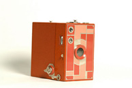 Photograph of a box camera with a two-tone rose faceplate and a matching leatherette exterior